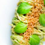 Overhead pea pesto served as a sauce for pasta with a breadcrumb crust featuring a title overlay.