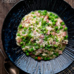 Overhead pea and ham risotto served in a blue bowl featuring a title overlay.