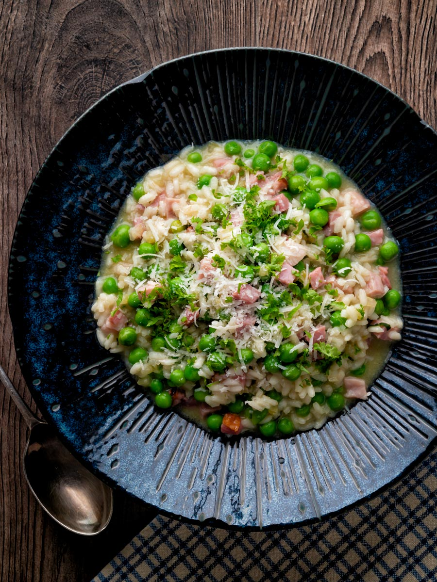 Overhead pea and ham risotto served in a blue bowl.