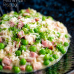 Pea and ham risotto served in a blue bowl garnished with goats cheese and parsley featuring a title overlay.