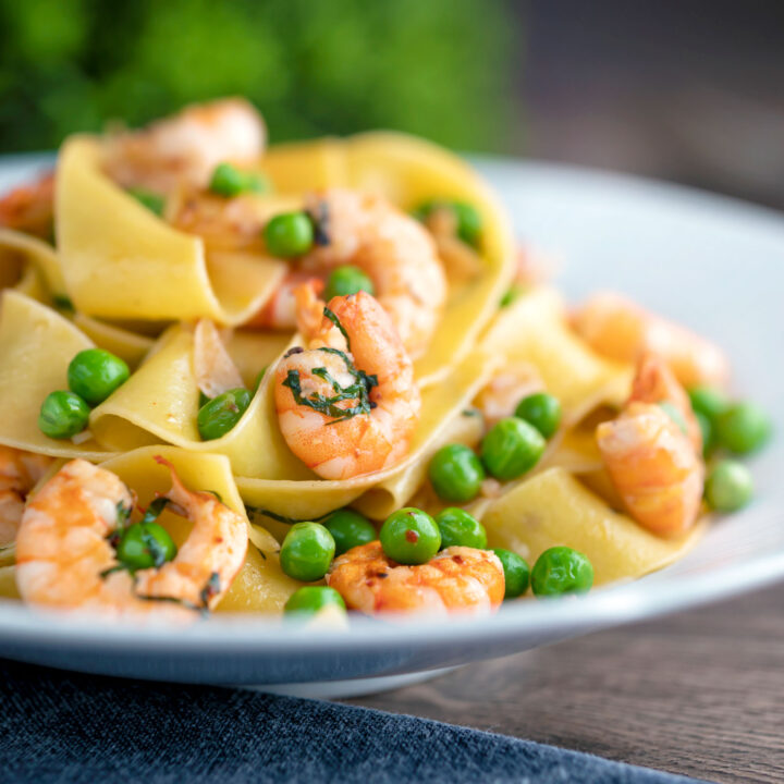 Prawn and pea pasta with pappardelle and chipotle chilli flakes served in a textured bowl.