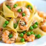 Prawn and pea pasta with pappardelle and shredded basil featuring a title overlay.