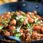 Vegan Punjabi chole masala curry or chana masala served in an iron karai featuring a title overlay.