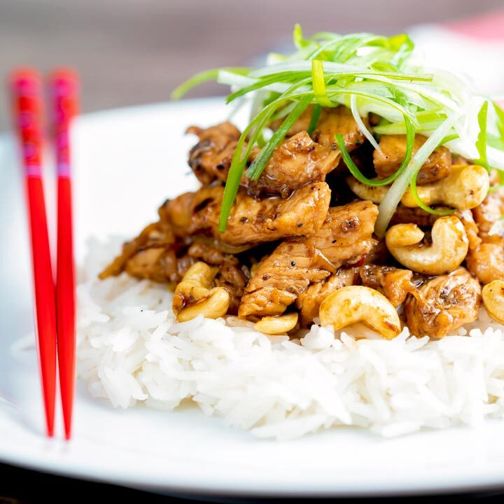 Szechuan chicken with cashew nuts served with white rice featuring red chopsticks.