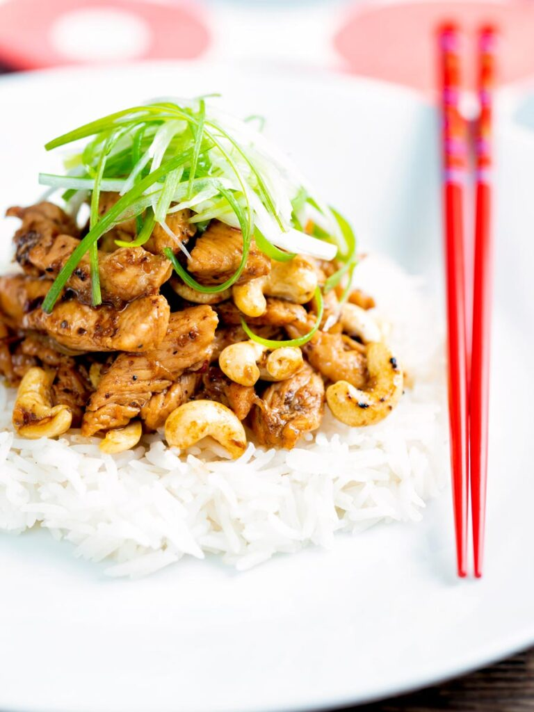 Szechuan chicken with cashew nuts and spring onion served on white rice.