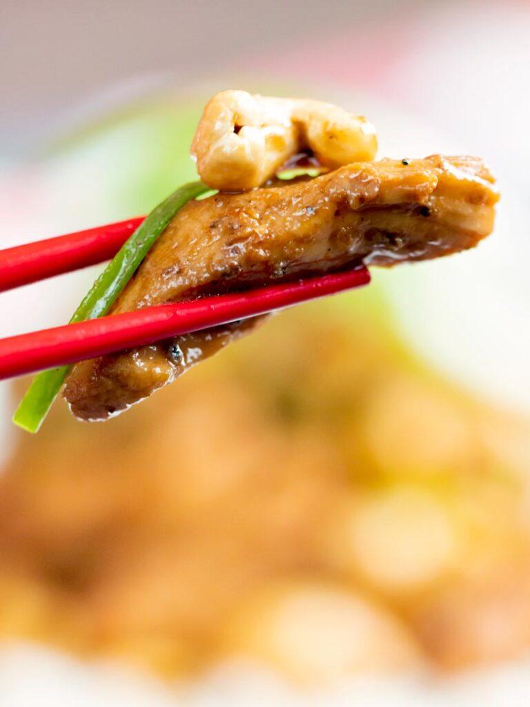 Close up Szechuan chicken with being held with chopsticks.
