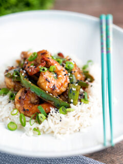 Szechuan prawns with green pepper served on steamed rice in a white bowl.