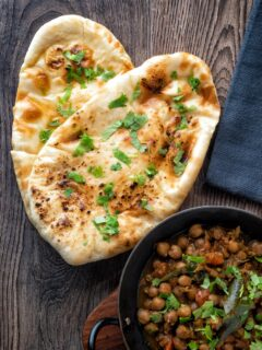 Overhead tandoori naan bread with coriander served with chole.