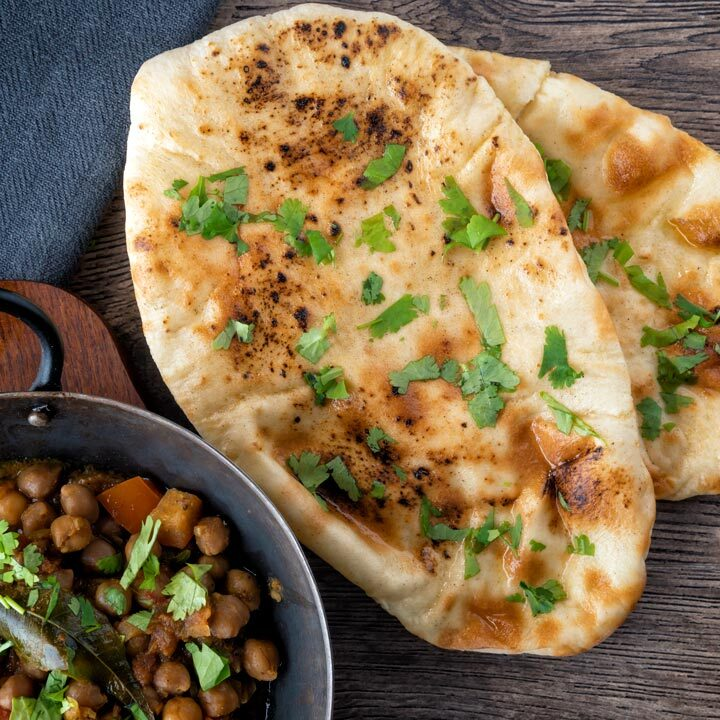 Overhead British Indian Curry house style Tandoori naan bread with coriander and ghee.
