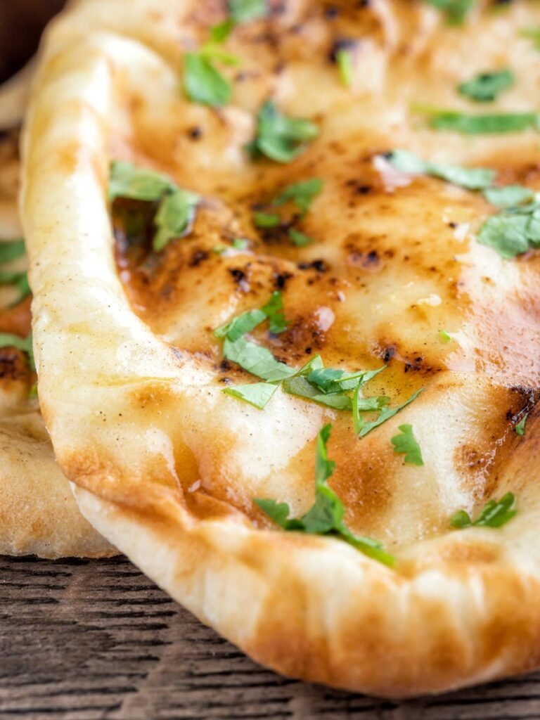 Close up British Indian Curry house style Tandoori naan bread with coriander.