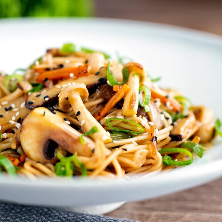 Stir fried vegetarian mushroom chow mein noodles served in a white bowl.