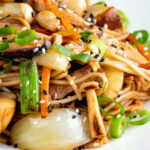 Close up vegetarian mushroom chow mein noodles using 3 types of mushroom featuring a title overlay.