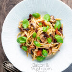 Overhead bacon and mushroom pasta with sun dried tomatoes featuring a title overlay.