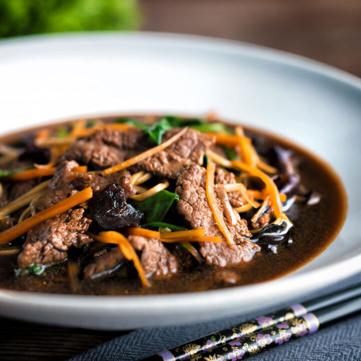 Beef noodle soup featuring spinach & dried mushrooms in a dark soy broth.