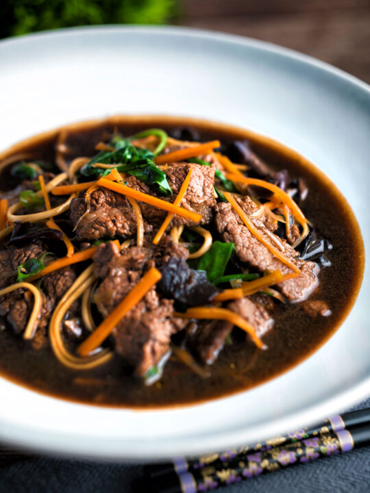 Beef noodle soup featuring udon noodles, spinach & carrot in a dark soy broth.
