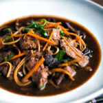 Beef noodle soup featuring udon noodles, spinach & carrot in a dark soy broth featuring a title overlay.