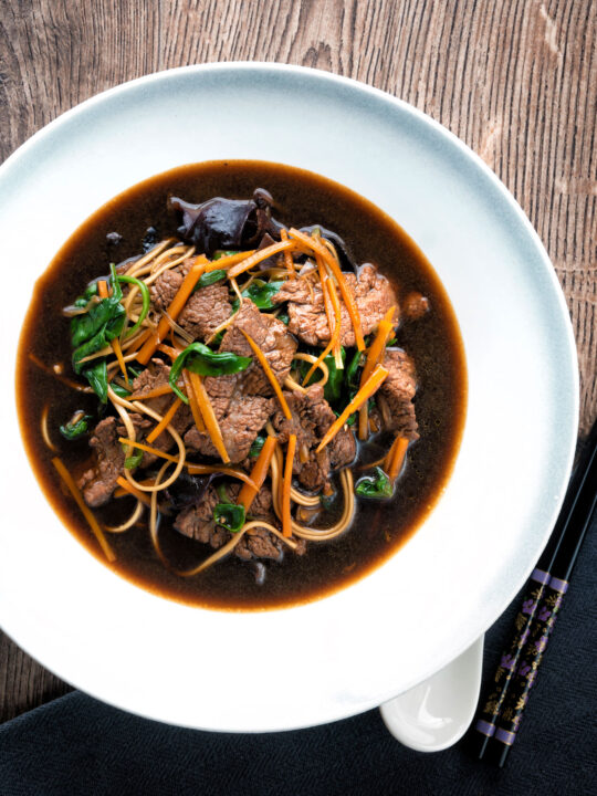 Overhead beef noodle soup featuring udon noodles & spinach in a dark soy broth