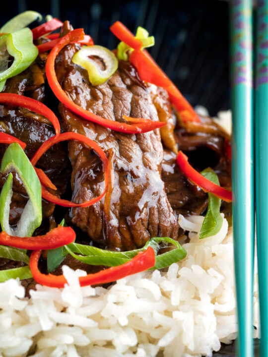 Close up beef in oyster sauce Chinese takeaway stir fry served with rice.