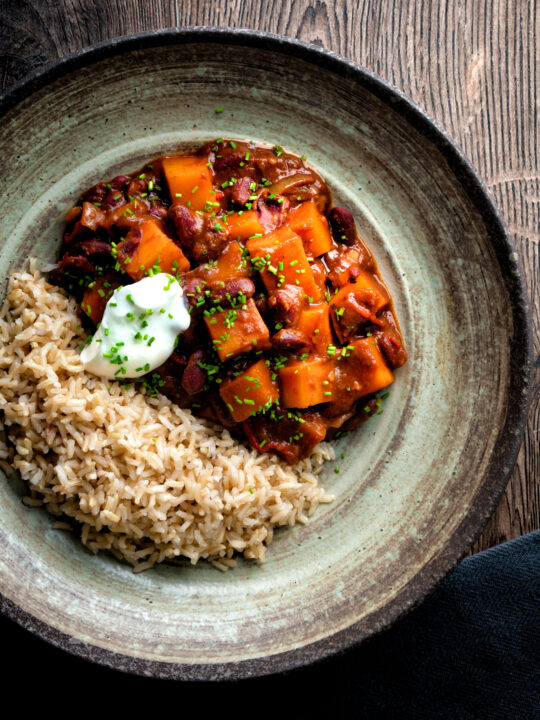 Overhead butternut squash chilli served with brown rice, and sour cream.