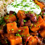 Close up butternut squash chilli served with brown rice, and sour cream.