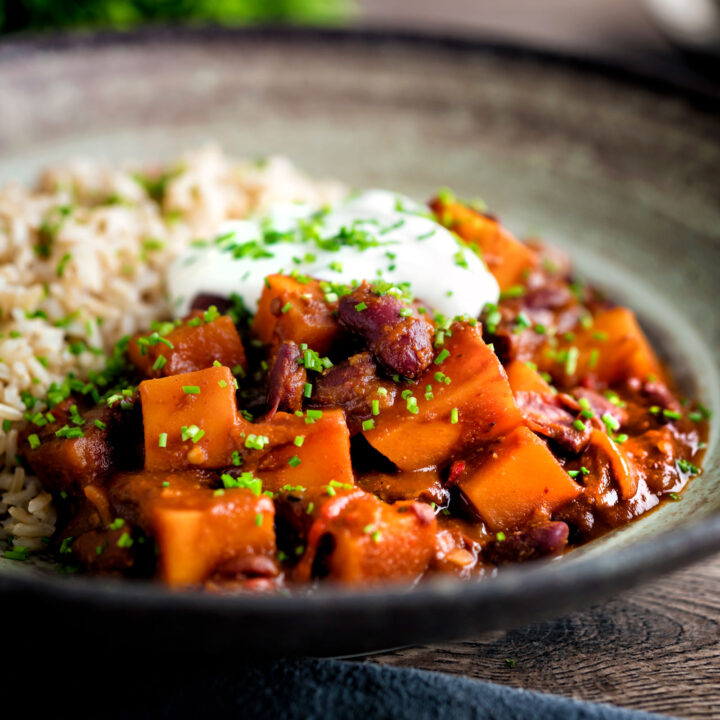 Butternut squash chilli served with brown rice, and sour cream in an earthenware bowl.