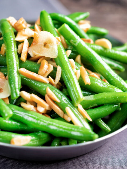 Close up garlic green beans served in a small pan garnished with almonds.
