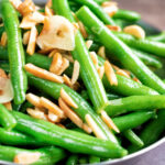 Close up garlic green beans served in a small pan garnished with almonds featuring a title overlay.