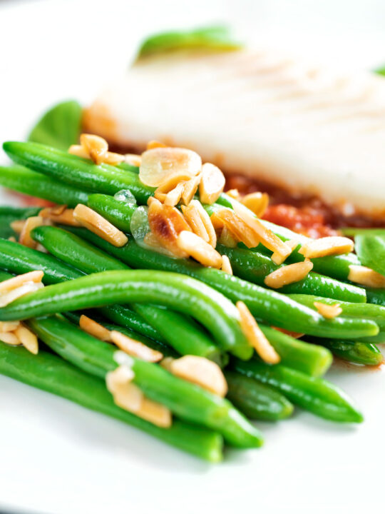 Garlic green beans served on a white plate garnished with almonds.