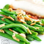 Garlic green beans served on a white plate garnished with almonds featuring a title overlay.