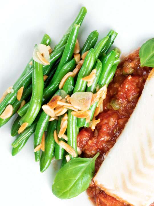 Overhead garlic green beans served on a white plate garnished with almonds.