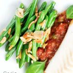 Overhead garlic green beans served on a white plate garnished with almonds featuring a title overlay.