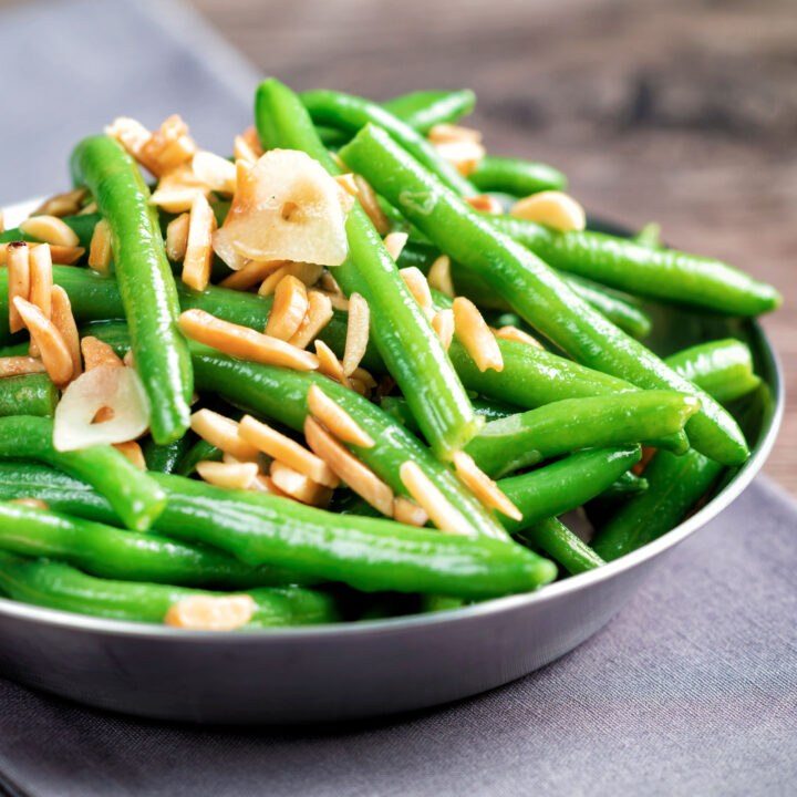 Garlic green beans served in a small pan garnished with almonds.