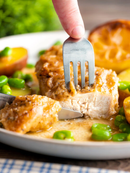Garlic lemon chicken breast cut open to show the moist perfectly cooked meat.