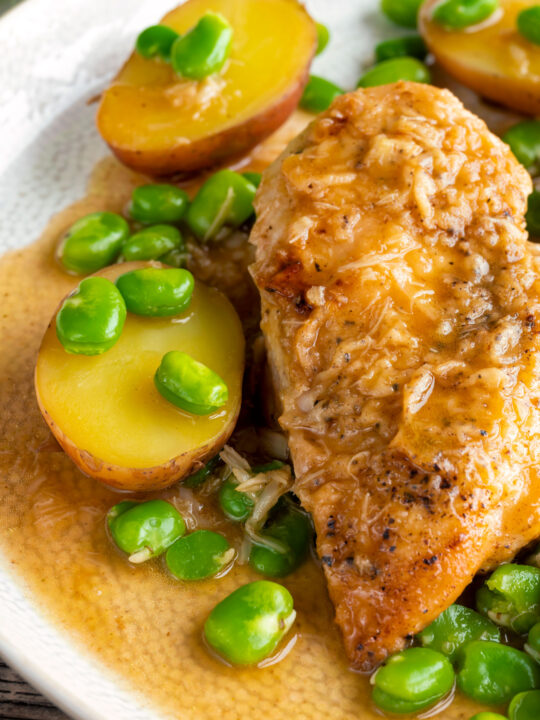 Close up garlic lemon chicken breast served with potatoes and broad beans