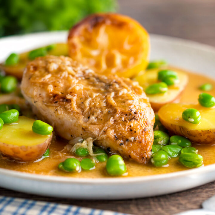 Garlic lemon chicken breast served with potatoes and broad beans in a sauce.