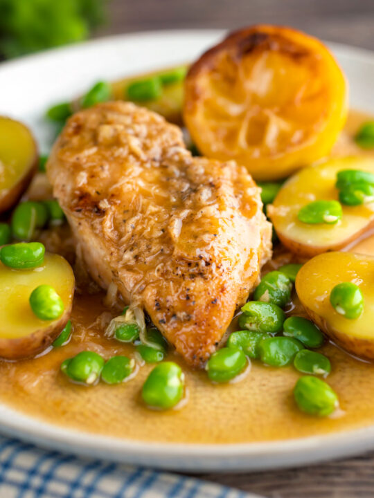 Garlic lemon chicken breast served with potatoes and broad beans.