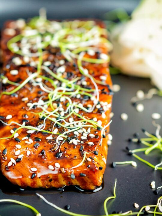 Close up honey soy salmon served on a black plate with pickled daikon and onion sprouts.