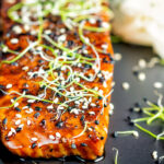 Close up honey soy salmon served on a black plate with pickled daikon and onion sprouts featuring a title overlay.