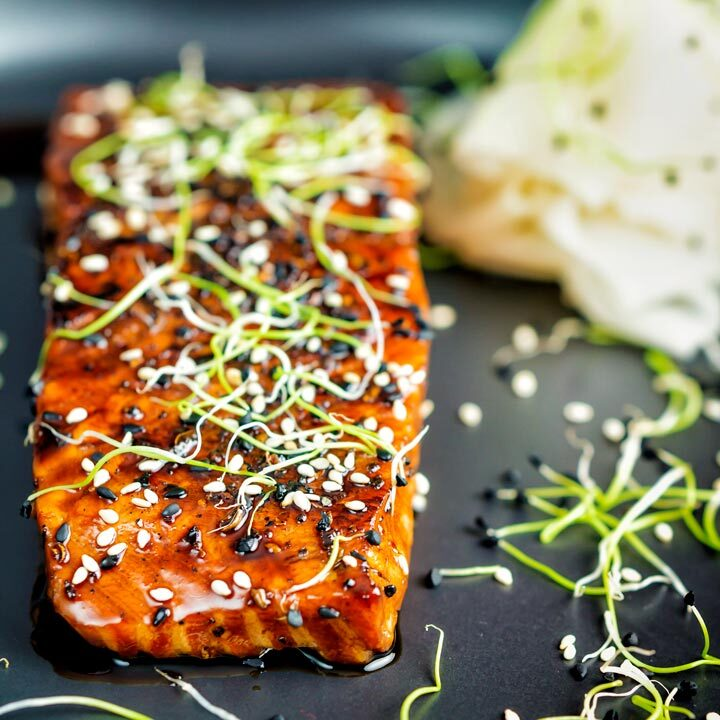 Honey soy salmon served on a black plate with pickled daikon and onion sprouts.