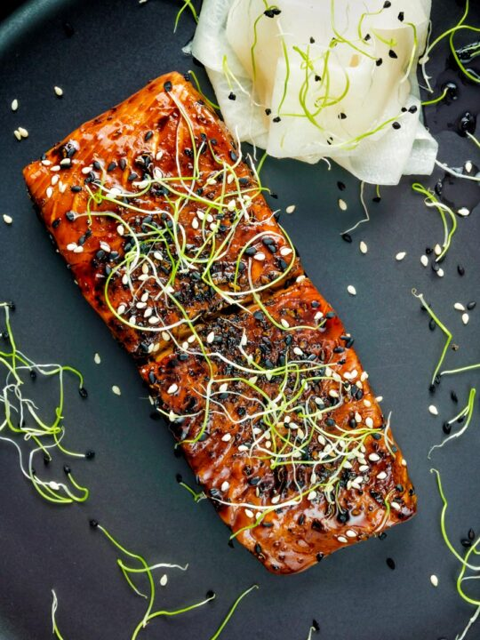 Overhead honey soy salmon served on a black plate with pickled daikon and onion sprouts.