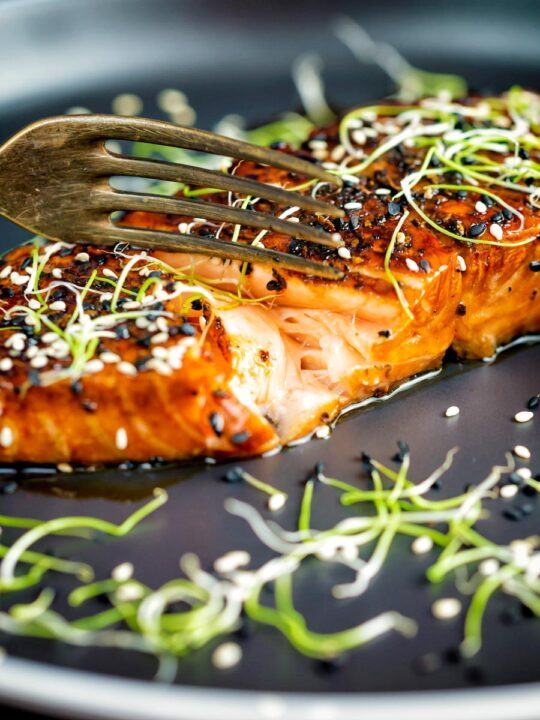 Honey soy salmon served on a black plate showing internal texture.