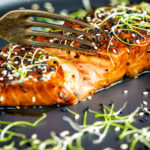 Honey soy salmon served on a black plate showing internal texture featuring a title overlay.