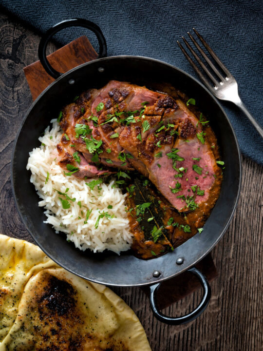 Overhead image of an Indian duck breast curry served with rice and naan bread.