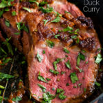 Close up Indian duck breast curry served in an iron karai featuring a title overlay.