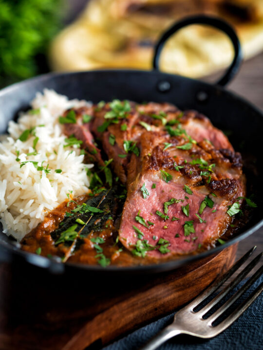 Indian duck breast curry served with rice and naan bread.