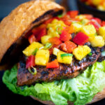 Jamaican jerk chicken burger with a mango salsa served on a toasted bun featuring a title overlay.