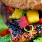 Close up Jamaican jerk chicken burger with a mango salsa featuring a title overlay.