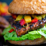 Jamaican jerk chicken burger with a mango salsa and crispy lettuce featuring a title overlay.