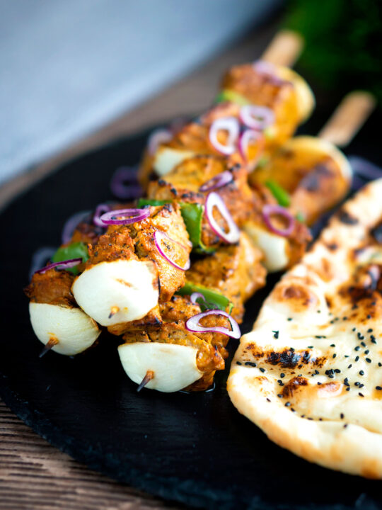 Lamb tikka kebabs with onion and green pepper served with a naan bread.