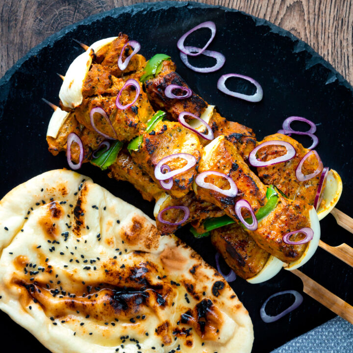 Lamb tikka kebabs with onion and green pepper served with a naan bread and red onion.